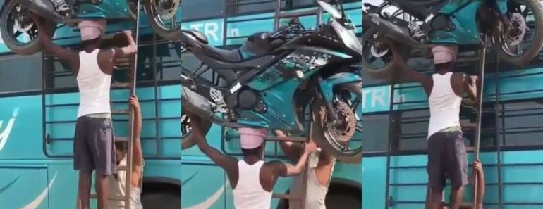 Ghanaian in India breaks the internet as he climbs a ladder with a huge motorbike on his head (Video)